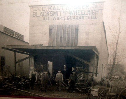 Photo of Deanville Blacksmith, John Maresh Jr. (Center) in training under C. Kaltwasser Blacksmith and Wheelwright
